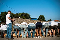 Group of men preparing to lift the trunk at Bonfire planting tradition of Lledías. Llanes. Asturias. Spain.