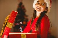 Festive little girl opening a glowing christmas gift