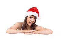 Festive brunette leaning on large poster