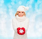 happiness, winter holidays, christmas and people concept - smiling young woman in hat, scarf and mittens holding snowflake decoration over blue lights...