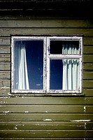 A window in an old wooden building with flaking and peeling paint.