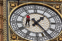 Worker suspended on ropes high above the ground cleaning the face of Big Ben clock tower, London, England, Europe.