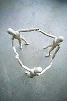 Three wooden manikins holding hands on grey ground