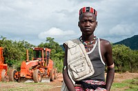 Boy belonging to the Banna tribe. Omo valley in Ethiopia. In the background, engines used for road works.