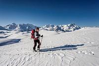 Ski tourner ascending Mt Seekofel in the Fanes-Sennes-Prags Nature Park in the Dolomites, Fanes Region with the mountains Piz de Lavarela and Piz dles...