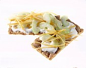 Close-up of two crisp breads with yogurt, perennial celery and carrot strips