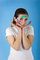 Beautiful woman with colored bandages on the face over a blue background