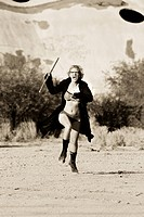 Female science fiction model in a desolate location attacking with a wooden stick.