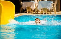 Girl Sliding in pool during Turkey vacations summer holiday