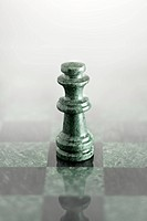 A chess piece on a marble chess board.