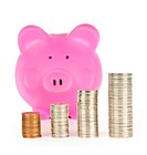 Stacks of coins in front of pink piggy bank showing growth