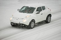 Germany, white car driving on snow-covered country road