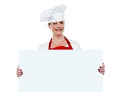 Happy matured cook presenting blank billboard against white background