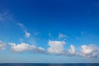 cumulus clouds in blue sky over ocean water horizon