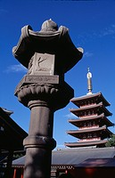Asakusa. Senso Ji Temple. Angled view of the Five Storey Pagoda with ornamental stone column in the foreground