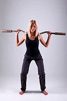 Slim and sporty young blonde doing fitness exercise with fitbar in studio