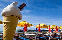 The Pier at low tide with shingle pebble beach and sunshade umbrellas by empty tables on the seafront with a fibreglass ice cream cone in the foregrou...