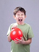 A young boy lets the blast of air from a balloon mess up his hair.