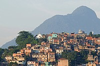 Favela or slum above Saude neighbourhood brick houses trees Church and mountain in the background.