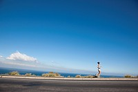 Woman Running along Asphalt Road by Ocean