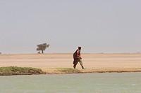 Man walking along the shores of the Niger River between Mopti and Lake Debo, Mali