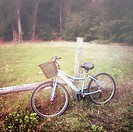 A bicycle sitting beside a barb wire fence in the countryside.