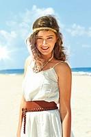 Young woman on beach wearing white sundress