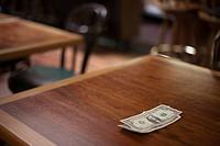 Cash gratuity on empty restaurant table