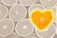 Orange cross section shaped like heart on slice background