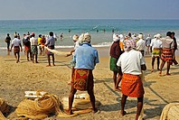 men pulling large fishing net from water, Hawa Beach, Kovalam, Kerala, India.