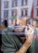 Young man looking through windowpane