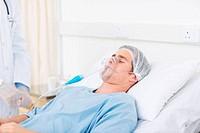 Male doctor adjusting oxygen mask on patient