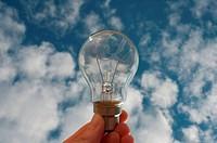 Lightbulb held against sky