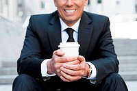 Relaxing with cup of coffee. Cropped image of cheerful mature man in formalwear holding coffee cup and smiling while sitting at the staircase outdoors