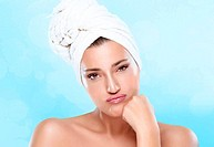 Young worried woman with towel on head pouts looking at camera. Closeup portrait. Haircare and bodycare