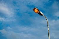 Street light pole with a blue sky background.