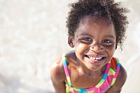 A cute little african girl in a swimsuit smiling at the camera