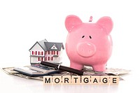 Piggy bank beside calculator miniature house and mortgage spelled out in plastic letter pieces on white background