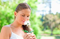 Woman smelling on a flower in the park