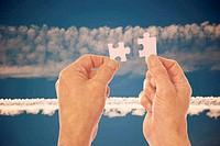 Hands connect puzzle pieces agains vapor trails