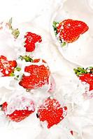 strawberries falling in cream