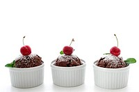 Chocolate muffins with cherry and leaves of mint on white background