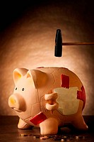 Piggy bank with money and hammer