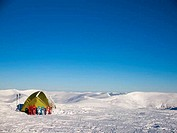 Snowshoes and tent on snow in the mountains.