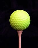 Yellow golf ball on a tee