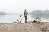 Young woman throwing stick for her dog on misty lakeside