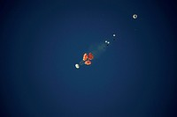 Orion spacecraft landing test. View of three parachutes (orange) gently lowering a mock-up Orion spacecraft capsule to the ground during testing. This...