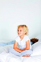 Little girl sitting in bed with copyspace