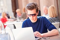 Young Man with Laptop Sitting in Outside Coffeehouse Working.