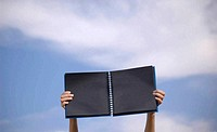 Black notebook in a blue sky